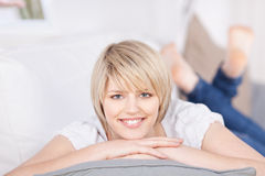 Femme blonde amicale se trouvant sur un sofa Photographie stock libre de droits