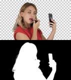 Femme blonde appliquant le rouge à lèvres regardant dans le téléphone, Alpha Channel images libres de droits