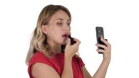 Femme blonde appliquant le rouge à lèvres regardant dans le téléphone sur le fond blanc clips vidéos