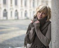 Femme blonde assez jeune dehors, utilisant l'écharpe de laine et le chandail Images libres de droits