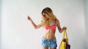 Femme blonde assez jeune marchant sur la plage pendant l'été ayant l'amusement et le sourire habillé dans les shorts de jeans et  clips vidéos