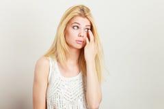 Femme blonde attirante ayant quelque chose dans l'oeil photos libres de droits