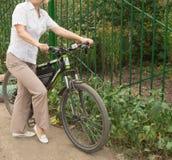 Femme blonde attirante d'une cinquantaine d'années sur une bicyclette en parc photos stock