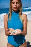 Femme blonde attirante dans des vêtements de bain bleus avec des coquillages dans des mains sur le littoral Photo libre de droits