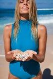Femme blonde attirante dans des vêtements de bain bleus avec des coquillages dans des mains sur le littoral Photographie stock libre de droits