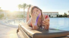 Femme blonde attirante dans la musique de écoute de maillot de bain rouge de son smartphone dans des écouteurs blancs, tout en se banque de vidéos