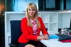 Femme blonde attirante dans le sourire de bureau Photo stock