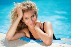 Femme blonde attirante de sourire heureuse dans la piscine de l'eau bleue images libres de droits