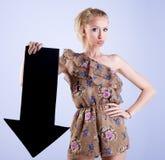 Femme blonde attirante posant avec la flèche image stock