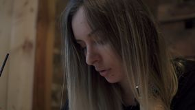 Femme blonde aux cheveux longs s'asseyant dans un café moderne et faisant pensivement quelques notes dans son carnet Un verre de banque de vidéos