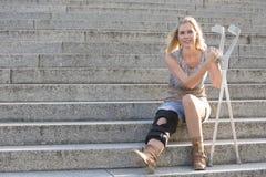 Femme blonde avec des béquilles image stock