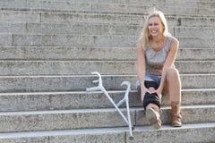 Femme blonde avec des béquilles photo stock