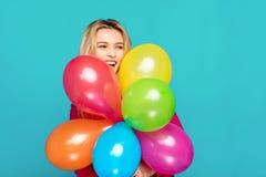 Femme blonde avec des ballons sur le bleu Images libres de droits