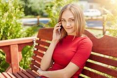 Femme blonde avec des taches de rousseur ayant le sourire doux tout en se reposant au banc confortable en bois dans le parc et co Photo stock