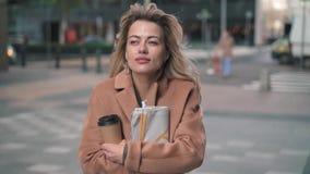 Femme blonde avec du café tremblant avec le froid dans la rue de chute banque de vidéos