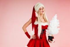 Femme blonde avec du charme et attirante dans un costume de Santa avec l'arbre de Noël blanc photos libres de droits