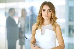 Femme blonde avec l'ordinateur de touchpad regardant l'appareil-photo et souriant tandis que les gens d'affaires de secousse reme Images stock