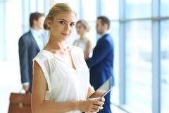 Femme blonde avec l'ordinateur de touchpad regardant l'appareil-photo et souriant tandis que les gens d'affaires de secousse reme Image libre de droits