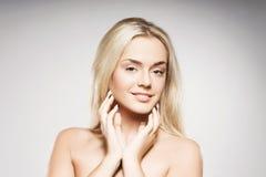Femme blonde avec la peau pure posant sur le fond gris Images libres de droits