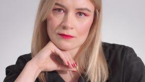 Femme blonde avec le maquillage rouge lumineux dans le studio clips vidéos