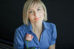 Femme blonde avec le portrait rose de studio de fleur Image stock