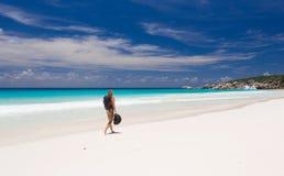 Femme blonde avec le sac à dos et le chapeau, promenades le long d'une plage Photographie stock libre de droits