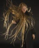 Femme blonde avec le vent soufflant par de longs cheveux Photographie stock libre de droits