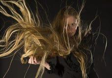 Femme blonde avec le vent soufflant par de longs cheveux Photos stock