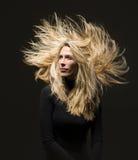 Femme blonde avec les cheveux extrêmes, la robe noire et le fond Photo stock