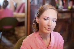 Femme blonde avec les cheveux lisses utilisant un peignoir pelucheux rose image libre de droits