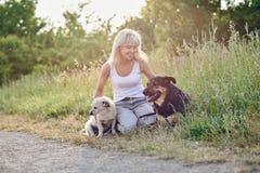 Femme blonde avec ses deux chiens dans la campagne Images libres de droits