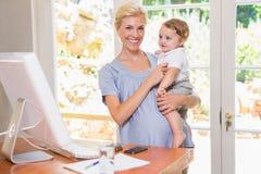 Femme blonde avec son fils à l'aide de l'ordinateur Photographie stock
