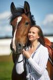 Femme blonde avec un cheval Photographie stock libre de droits