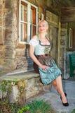 Femme blonde bavaroise s'asseyant d'une manière élégante dans un dirndl Image libre de droits