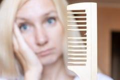 Femme blonde brouillée avec un peigne cassé dans sa main photographie stock libre de droits