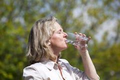 Femme blonde buvant une glace de l'eau Photographie stock libre de droits