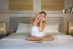 Femme blonde caucasienne attirante 30s et heureuse dans la chambre à coucher de lit à la maison écoutant la chanson d'Internet de photo libre de droits