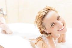 Femme blonde caucasienne de sourire prenant la baignoire avec la mousse Images stock