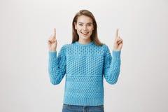 Femme blonde caucasienne heureuse impressionnée se dirigeant, chandail bleu de port, souriant largement et exprimant l'excitation photo libre de droits