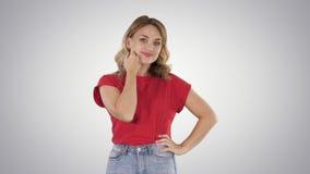 Femme blonde caucasienne positive et sensuelle regardant et examinant son visage et cheveux sur le fond de gradient banque de vidéos