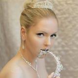 Femme blonde chaude attirante mangeant la couronne Bijoux, argent liquide, peau blanche, fond clair Photographie stock libre de droits