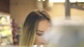 Femme blonde choisissant des produits dans le centre commercial Longueur de l'étagère, produits brouillés sur le premier plan Fro banque de vidéos