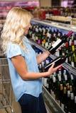 Femme blonde choisissant la bouteille de vin Photographie stock libre de droits