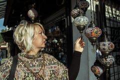 Femme blonde choisissant un souvenir à Sarajevo Photographie stock libre de droits