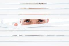 Femme blonde curieuse regardant par les abat-jour vénitiens photos libres de droits