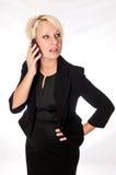 Femme blonde d'affaires dans un costume noir parlant à un téléphone portable Images stock