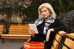 Femme blonde d'affaires de jeune mode utilisant la tablette numérique sur le banc photographie stock libre de droits
