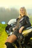 Femme blonde dans des lunettes de soleil sur une moto de sports Image libre de droits