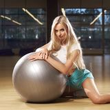 Femme blonde dans l'habillement de sports posant avec la boule argentée de yoga Photographie stock