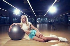 Femme blonde dans l'habillement de sports posant avec la boule argentée de yoga Images libres de droits